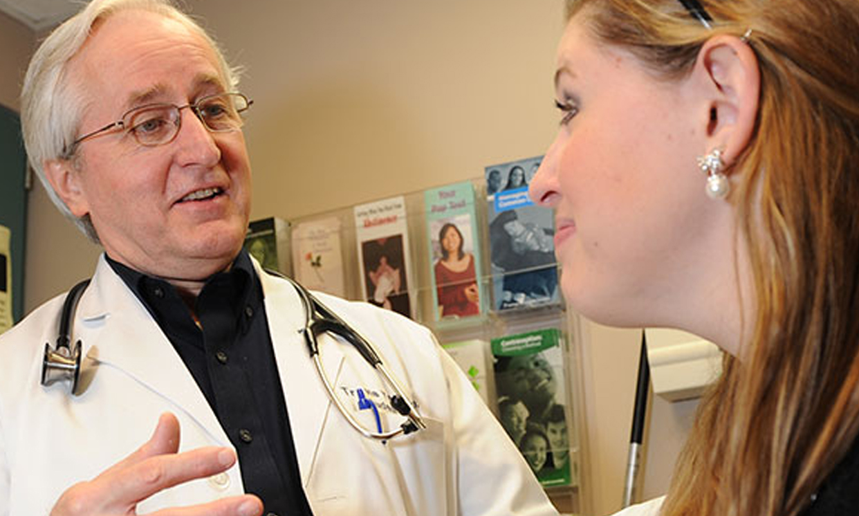 Medical professional in white coat talking to patient