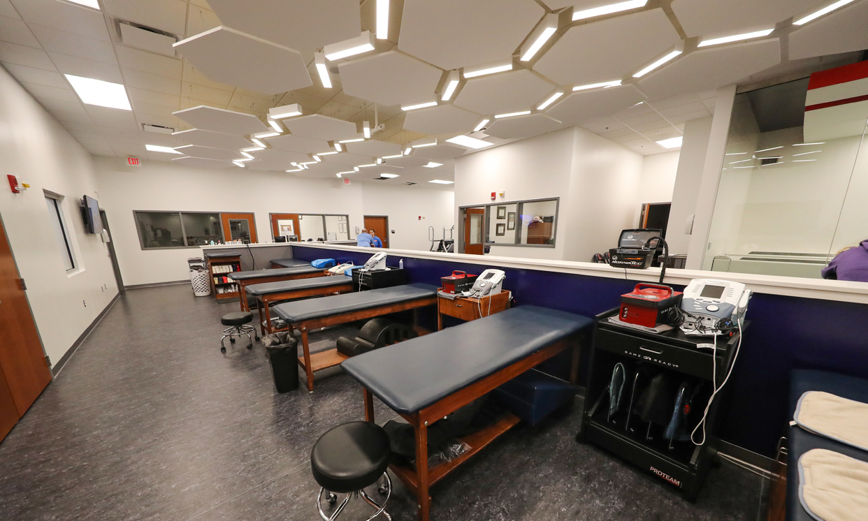 Room with medical equipment and patient tables in a row